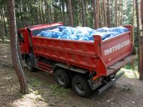 Nákladní mercedes odjíždí plný pytlů s odpadky