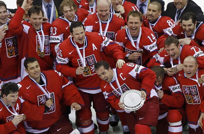 Se lvíčkem na prsou a bronzem na krku. Oslavující český tým.